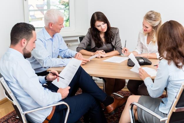 Advogados em reunião de equipe em escritório de advocacia lendo documentos