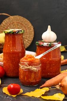 Adzhika caseiro com tomates, maçãs e cenouras em potes no escuro, colhendo para o inverno, foto vertical