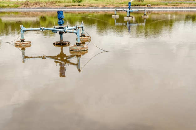 Aeradores de superfície na lagoa das águas residuais no local de aterro.