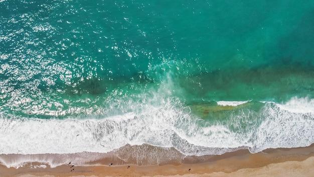 Aérea de drone de uma praia deslumbrante com bela paisagem marítima e água turquesa ao nascer do sol grátis