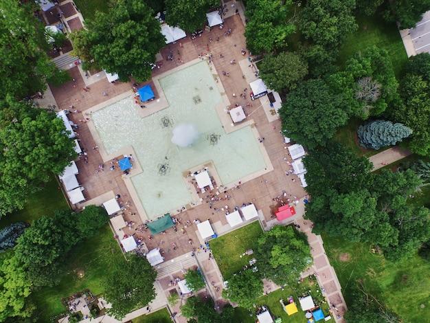 Aérea de uma grande piscina cercada por árvores com barracas coloridas armadas no concreto