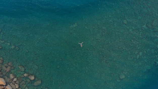Aérea: mulher flutuando na superfície da água azul, nadar no mar mediterrâneo transparente, vista de cima para baixo, conceito de férias de verão