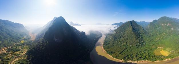 Aérea panorâmica nam ou rio drone sobrevoando a névoa da manhã de nevoeiro e nuvens, nong khiaw muang ngoi laos, paisagem dramática penhasco pináculo cênico, famoso destino de viagem no sudeste da ásia