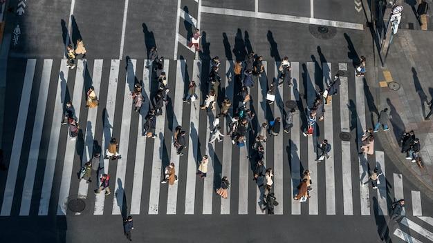 Aérea sobre a multidão da rua de passagem para pedestres japonesa com a luz do sol. vista elevada de asiáticos caminhando na interseção da estrada mais movimentada da cidade de tóquio
