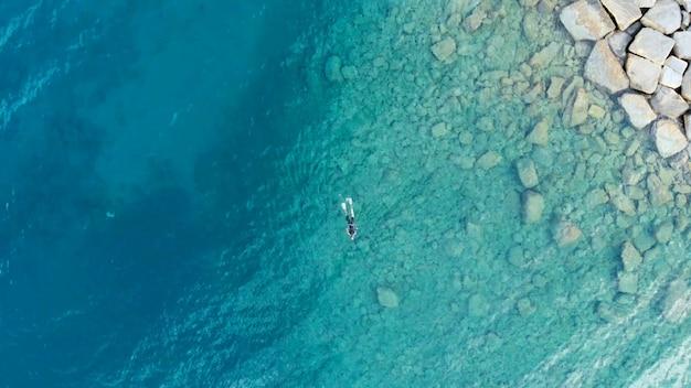 Aérea: uma pessoa mergulhador a pescar no mar mediterrâneo cristalino, água transparente azul profundo, conceito de férias de esporte de verão