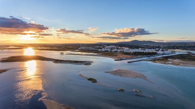 Aéreo. delicioso pôr do sol sobre a vila portuguesa da fuzeta, tavira.