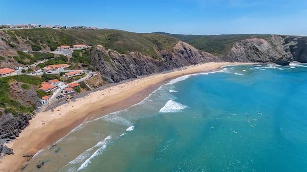 Aéreo. turistas surfistas na praia da arrifana. algarve