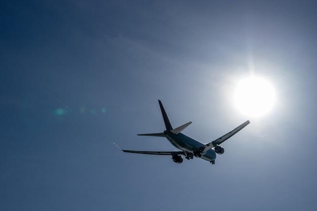 Aero plano decolar do aeroporto com vista do sol direto e céu azul.