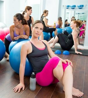 Aeróbica mulheres pilates grupo tendo um descanso no ginásio
