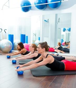Aeróbica pilates mulheres com bolas de tonificação em uma fileira