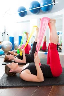 Aeróbica pilates mulheres com elásticos em uma fileira