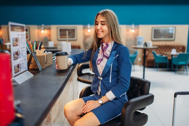Aeromoça bebe café no café do aeroporto