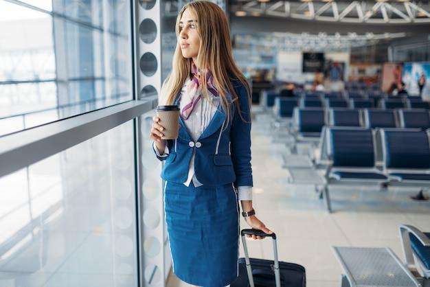 Aeromoça com bagagem de mão e café no aeroporto