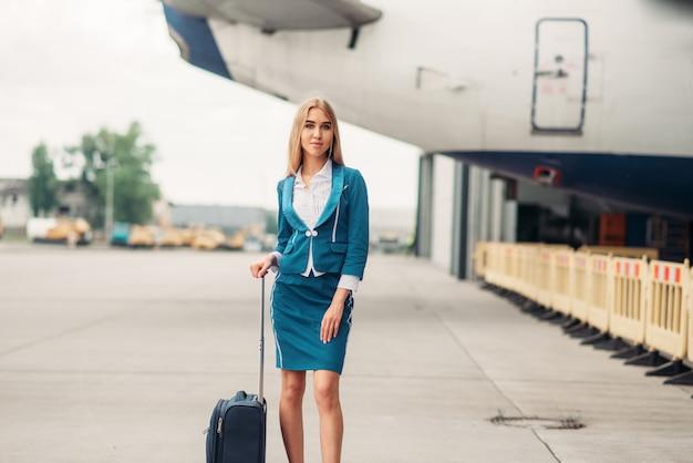 Aeromoça com mala no estacionamento de aeronaves