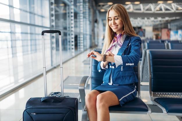 Aeromoça com mala sentada na sala de espera