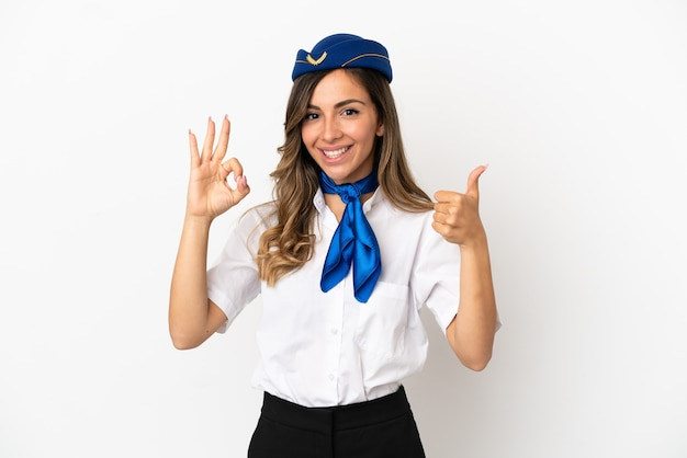 Aeromoça de avião sobre fundo branco isolado mostrando sinal de ok e gesto de polegar para cima