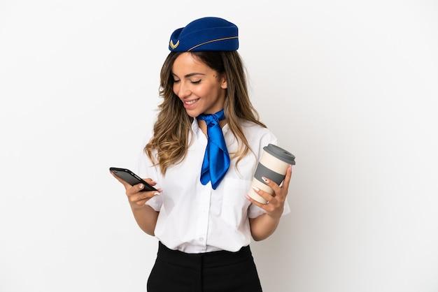 Aeromoça de avião sobre fundo branco isolado segurando café para levar e um celular