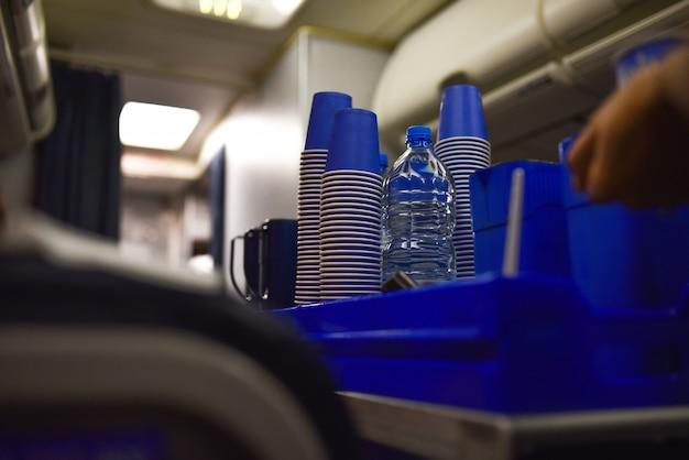 Aeromoça em um avião dá água potável a um passageiro