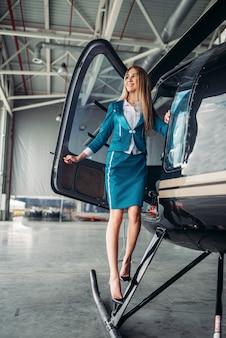 Aeromoça em uniforme posa contra o helicóptero