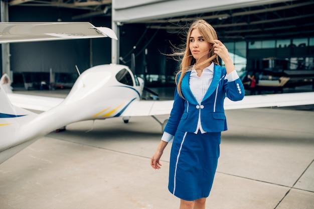 Aeromoça em uniforme posa contra um pequeno avião