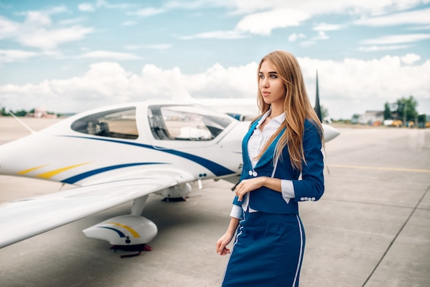 Aeromoça sorridente de terno contra um pequeno avião