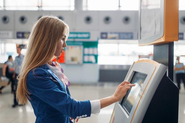 Aeromoça usa terminal no saguão do aeroporto