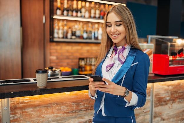 Aeromoça usando telefone celular no café do aeroporto