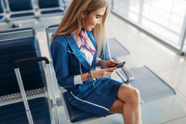 Aeromoça usando telefone na sala de espera do aeroporto