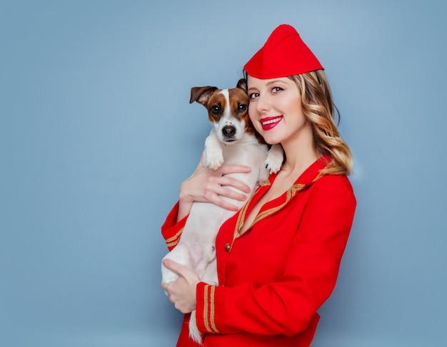 Aeromoça vestindo em uniforme vermelho com cachorro