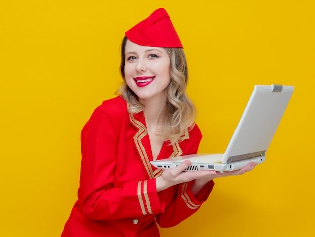 Aeromoça vestindo em uniforme vermelho com computador portátil