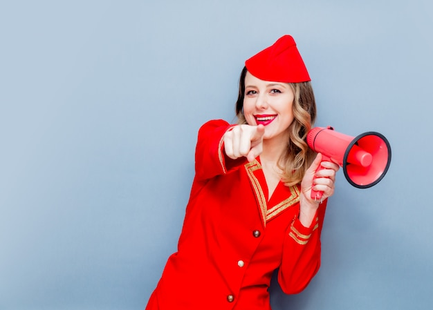 Aeromoça vestindo em uniforme vermelho com megafone