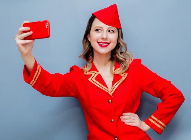 Aeromoça vestindo em uniforme vermelho com telefone celular