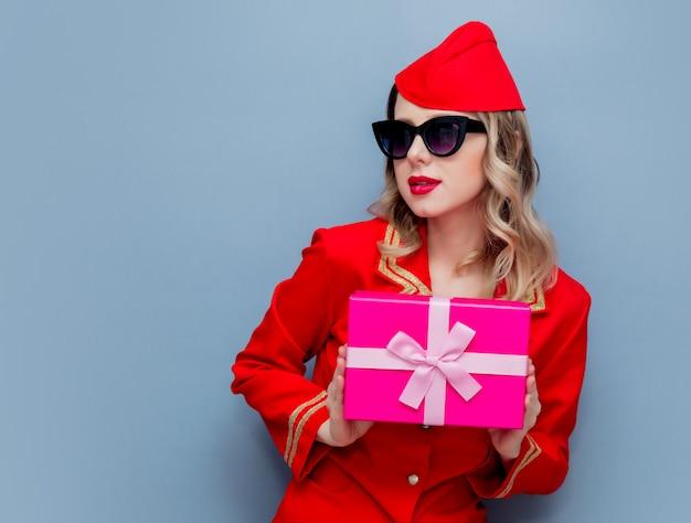 Aeromoça vestindo uniforme vermelho com placa de presente de feriado