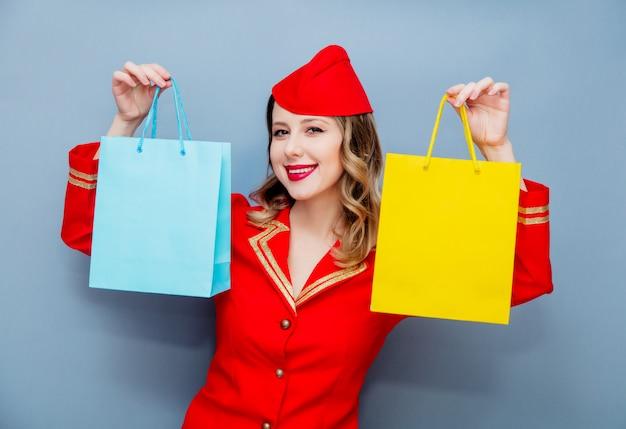 Aeromoça vestindo uniforme vermelho com sacolas de compras.