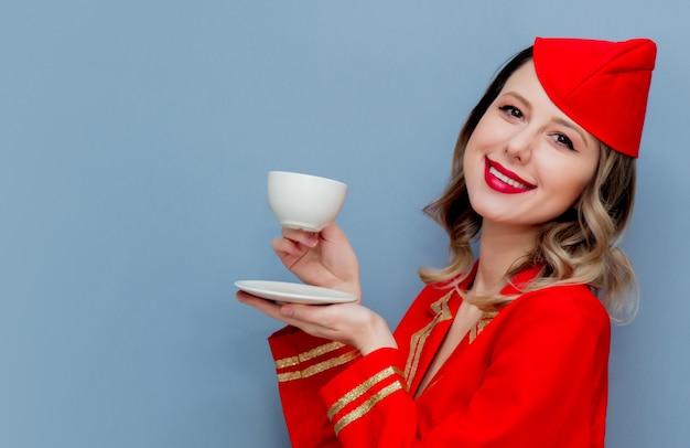 Aeromoça vestindo uniforme vermelho com xícara de café ou te