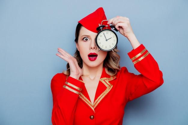Aeromoça vintage vestindo uniforme vermelho com despertador