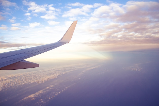 Aeronave asa vista do avião com o lindo céu do sol e nuvens