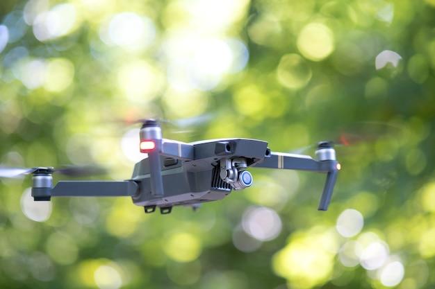 Aeronave drone com hélices de rotação rápida borradas e câmera fotográfica voando no ar.