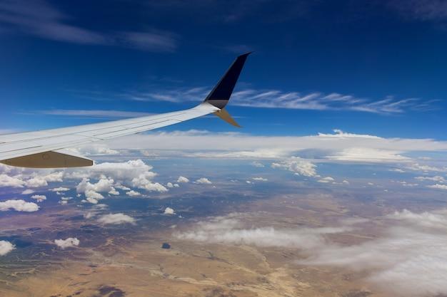 Aeronave em asa acima de nuvens brancas no céu de avião