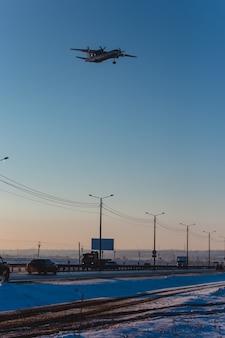 Aeronave turboélice pousando, voando sobre a rodovia.