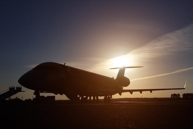 Aeroporto trabalhando na pista de pouso. avião na pista ao pôr do sol no aeródromo. grande sol amarelo no céu escuro. silhuetas de aeronaves no escuro, luz do sol