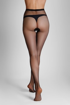 Afastando-se pernas longas e finas do sexo feminino em meia arrastão preta. vista traseira.