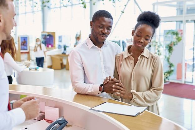 Afável vendedor profissional caucasiano mostra o documento aos clientes