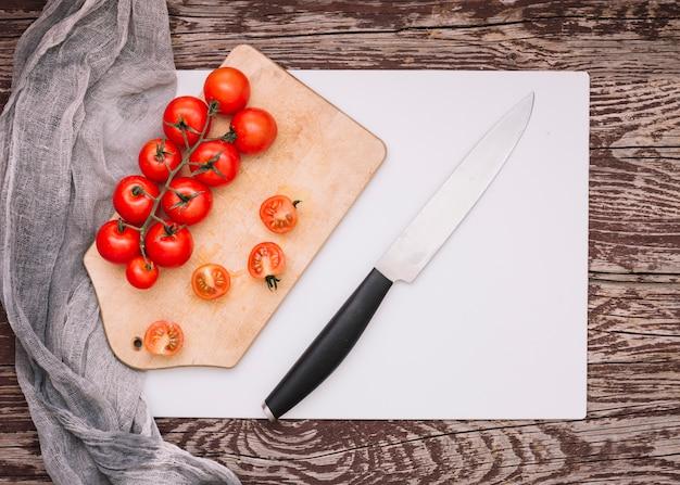Afiada faca e bando de tomate cereja em cortar a placa sobre o papel branco contra a mesa