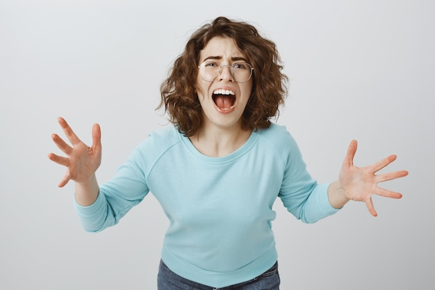 Aflita e louca, mulher de coração partido gritando e apertando as mãos, garota discutindo, repreendendo alguém
