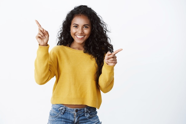 Afortunada alegre garota afro-americana com sorriso divertido e satisfeito apontando para o lado, mostrando o espaço da cópia à esquerda e à direita com espanto e alegria, promover com prazer a oferta bacana, indicando banners de produtos