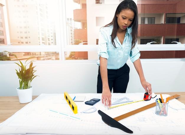 Africano-americana senhora com régua perto de plano na mesa com equipamentos