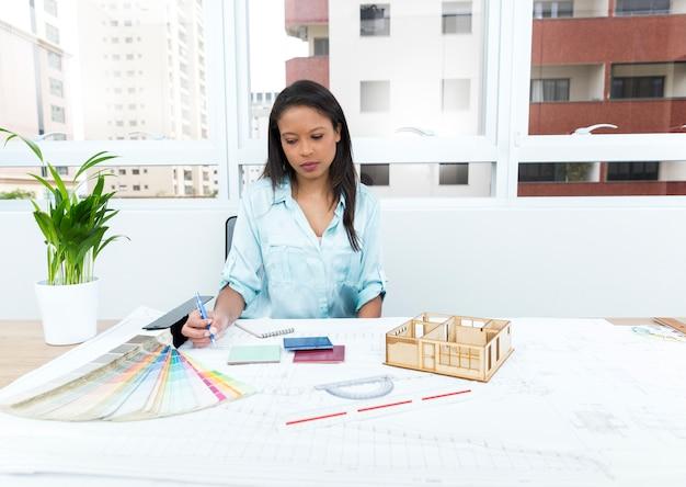 Africano-americana senhora na cadeira tomando notas perto de plano e modelo de casa na mesa
