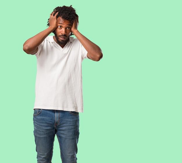 Africano-americano bonito frustrado e desesperado, irritado e triste com as mãos na cabeça