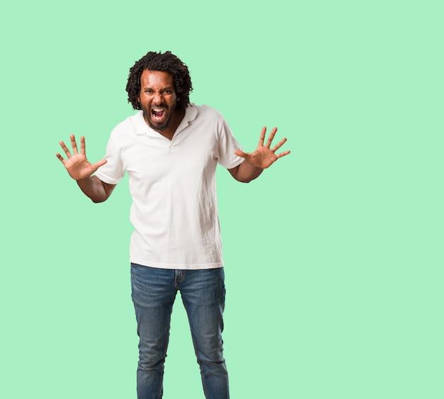 Africano-americano bonito gritando com raiva, expressão de loucura e instabilidade mental